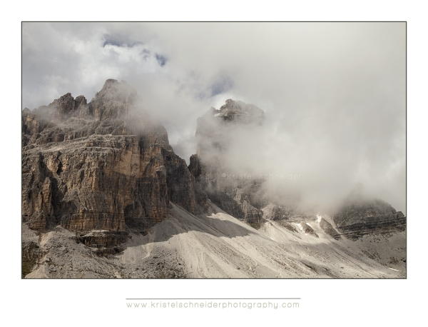 Tre cime in the clouds with afternoon sunlight just after a storm